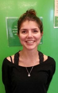 Giulia, standing in front of a green background smiling