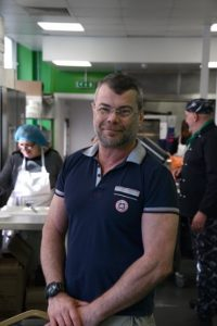 Man standing in busy kitchen, smiling at camera