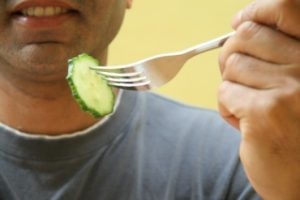Close up of man holding forked cucumber slice, smiling