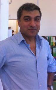 Man in button up shirt smilng at camera